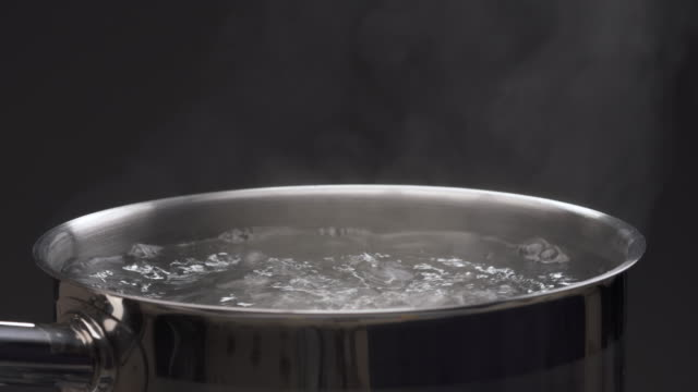 steam over cooking pot. isolated, on black background - bollente video stock e b–roll