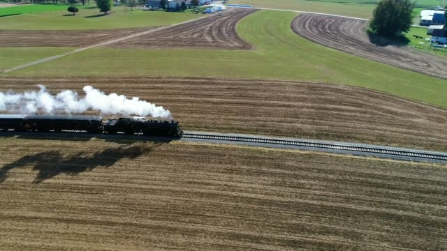 Steam Passenger Train Puffing Smoke Along Amish Countryside as Seen by a Drone