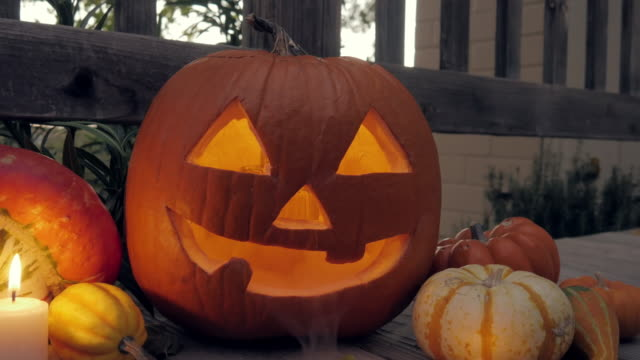 steam pours out of a lit halloween jack o'lantern - portico video stock e b–roll