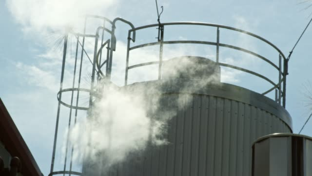 Steam Rises from a Beer Fermenter at a Manufacturing Facility Under a Sunny, Blue Sky Steam Rises from a Beer Fermenter at a Manufacturing Facility Under a Sunny, Blue Sky storage tank stock videos & royalty-free footage