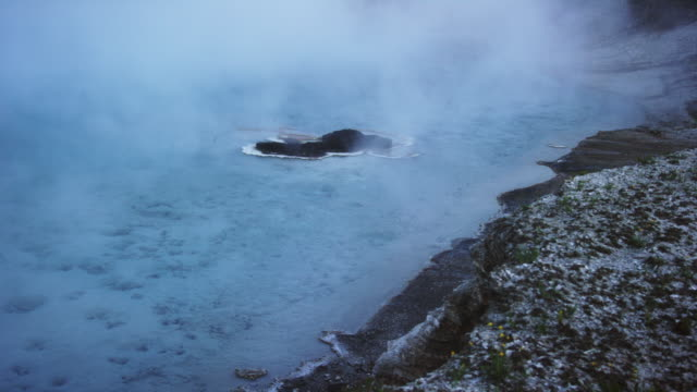 Steam Rises over Excelsior Geyser Crater at Yellowstone National Park in Wyoming at Dusk/Sunset