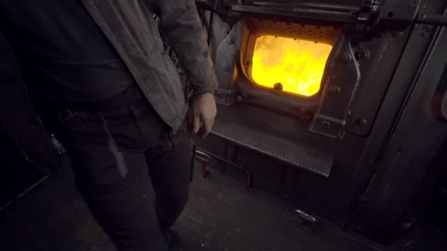 stockvideo's en b-roll-footage met stoom trein details van ingenieur shoveling kolen in de oven - shovel