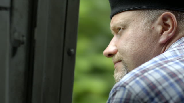 Steam train engineer looking out of the locomotive cabin at a forest