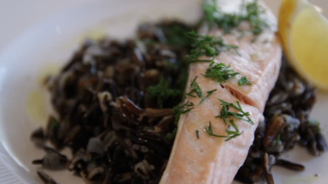steamed red fish, served with black rice and lemon. high protein foods. the camera moves around this to the left.
