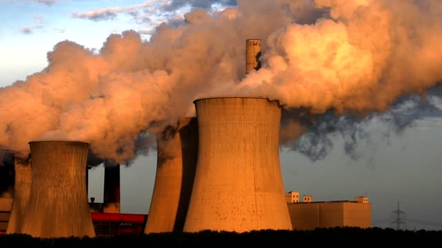 steaming coal power station in the evening light - emettere video stock e b–roll