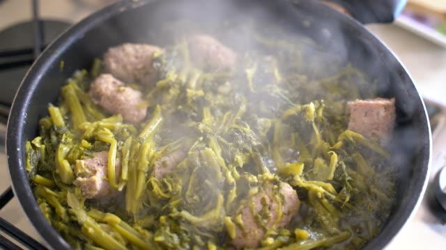 dampfende köstliche hausgemachte mahlzeit mit gekochtem spinat und würstchen, zubereitung des abendessens oder mittagessen zu hause. braten von gemüse mit fleisch auf kochpfanne auf küchenherd, konzept der gesunden ernährung und wohlbefinden - grünkohl stock-videos und b-roll-filmmaterial