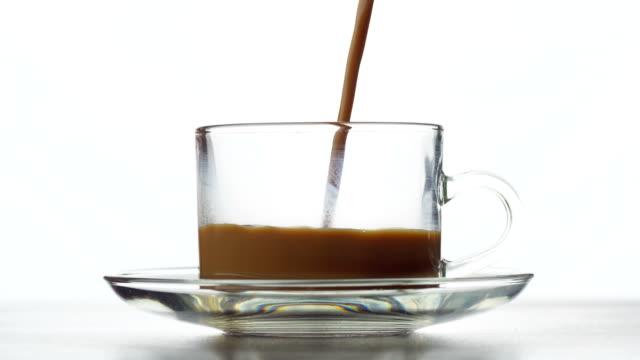 vidéos et rushes de café chaud, verser dans une tasse à la vapeur - pots de bureau