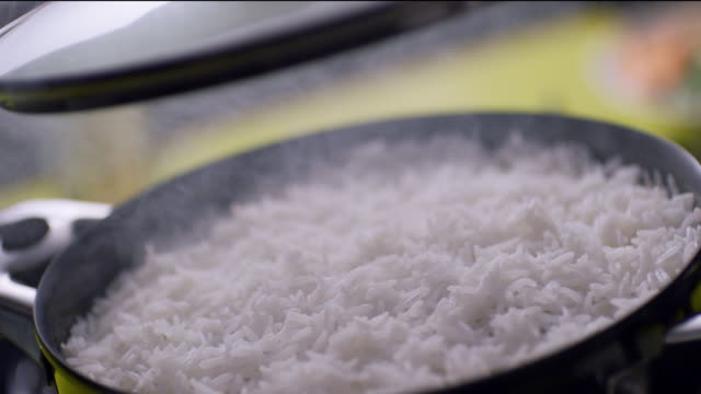 steaming hot rice in a casserole cookware. white rice with lid being lifted - coperchio video stock e b–roll