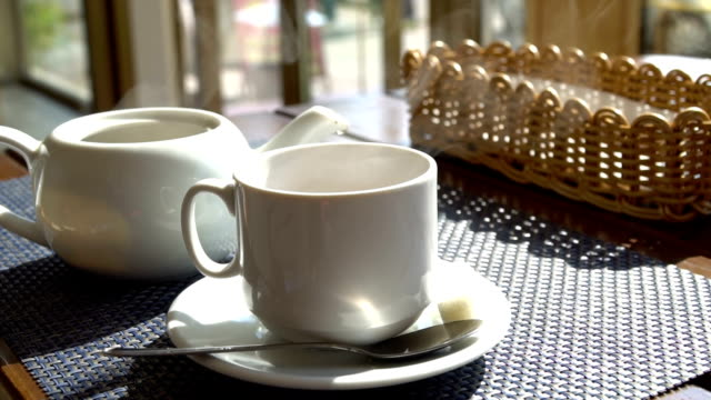 vídeos de stock e filmes b-roll de steaming white cup mug of tea coffee on the table in cafe. hot beverage - coffee table