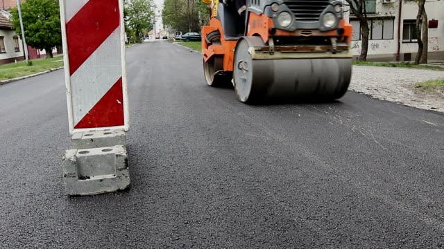 Steamroller is spreading hot asphalt video