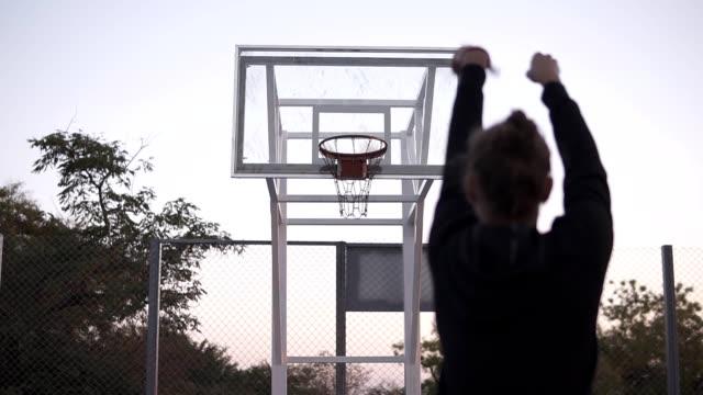 vídeos y material grabado en eventos de stock de stedicam imágenes de la joven de la parte trasera hacer un tiro a la canasta de baloncesto. árboles al aire libre, en el fondo - basketball hoop