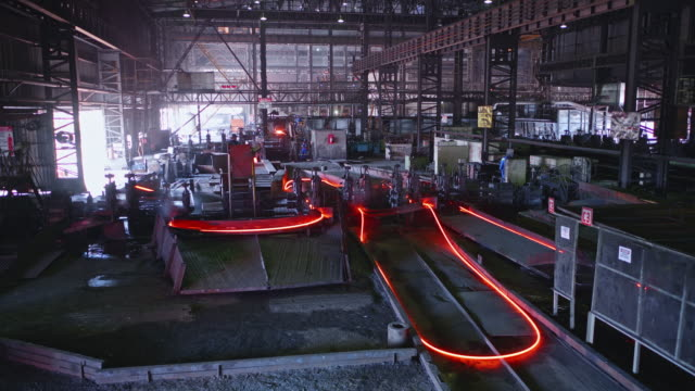 steel bars been shaped at a large steel factory in africa - cavo d'acciaio video stock e b–roll