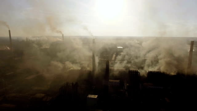 steel factory industry smoke at sunset. aerial view - дымоход стоковые видео и кадры b-roll