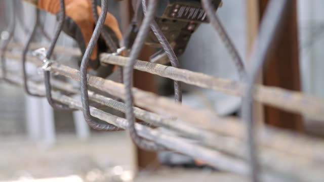 Steel fixers connecting steel rods for concrete reinforcements in a construction site Steel fixers connecting steel rods for concrete reinforcements in a construction site solid stock videos & royalty-free footage