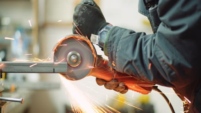 vídeos de stock e filmes b-roll de steel industry - man using angle grinder grinding metal object. - triturar atividade