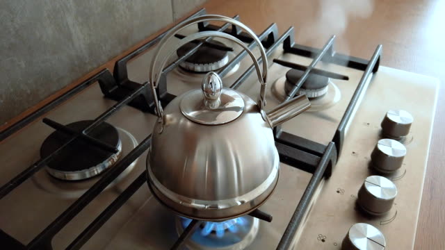 steel metal kettle boiling on a home gas stove, home boil water for tea indoor steam - teapot stock videos & royalty-free footage