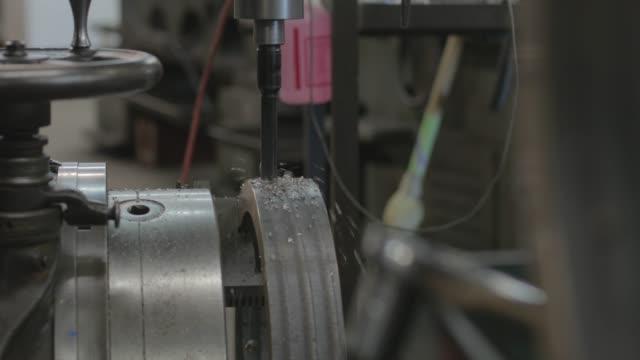 steel part being drilled - lega metallica video stock e b–roll