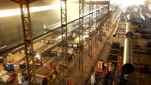 Steel Pipe Factory A view taken high up from a gantry crane, of a steel factory floor, making large diameter steel water pipes. steel mill stock videos & royalty-free footage