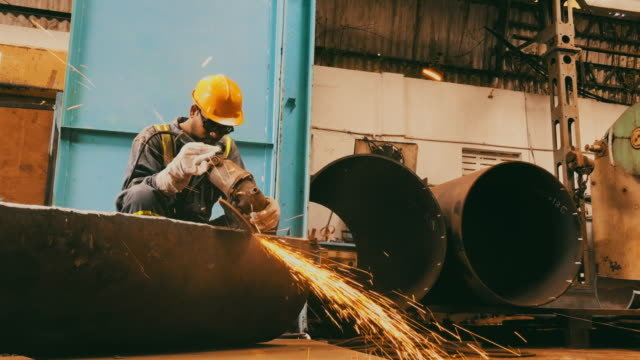 steel pipe factory worker grinding the semi finished pipe - rettificatrice video stock e b–roll