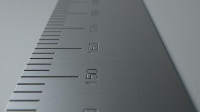 vídeos de stock e filmes b-roll de steel ruler with indented measurements on a white - reto descrição física