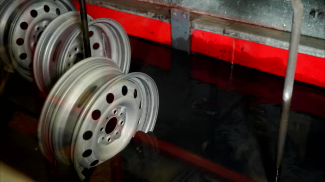 Steel wheels are plunging in automated bath during process of powder painting. video