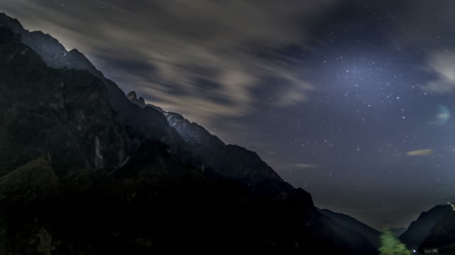 Steep cliffs at night and moving lots of clouds and stars.