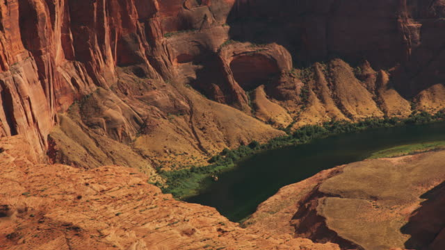 AERIAL Steep cliffs surrounding the Colorado River at the Horseshoe Bend in Arizona, USA