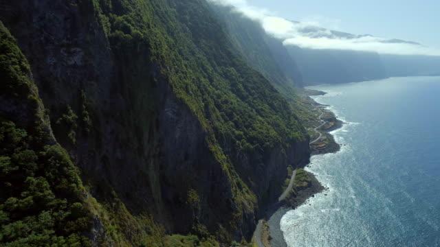 vídeos de stock e filmes b-roll de steep green mountainous coastline of madeira - ilha da madeira