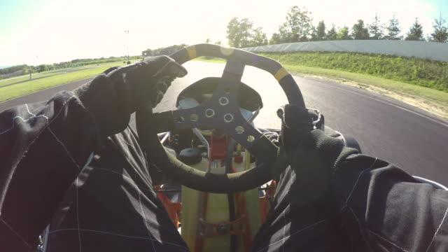 POV: Steering a speeding go cart along the winding asphalt circuit on sunny day.