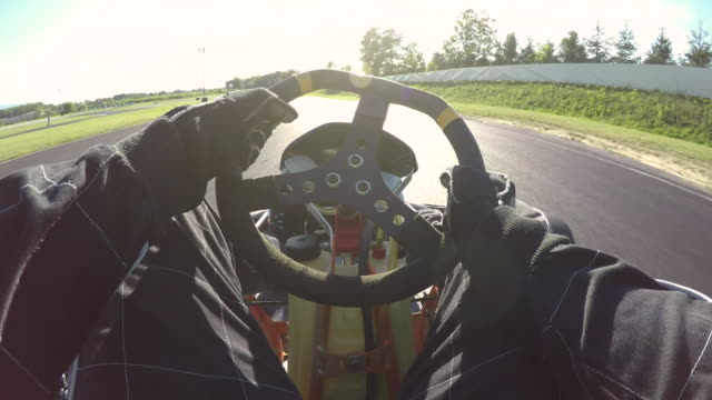 POV: Steering a speeding go cart along the winding asphalt circuit on sunny day. POV, LENS FLARE: Steering a speeding go cart along the winding asphalt circuit on a sunny day. Driving a fast cart in a black suit through sharp turns of a bumpy racetrack. Bright sun shines on racers go cart stock videos & royalty-free footage
