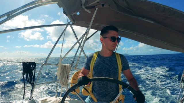 steersman is navigating a boat through the sea - ster fragment pojazdu filmów i materiałów b-roll