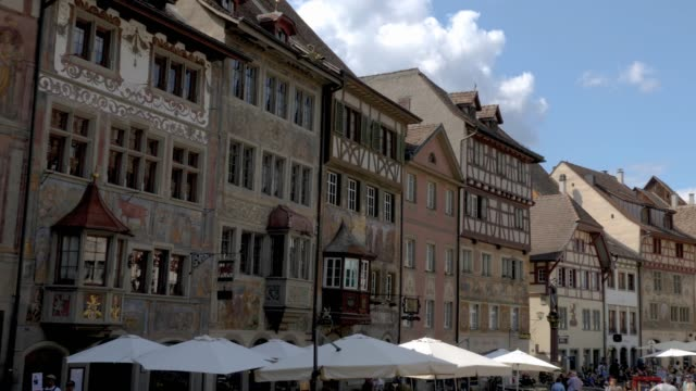 Stein am Rhein- buildings with frescoes on marketplace square Camera pans right at the Stein am Rhein marketplace, across the facades of fresco painted buildings. bay window stock videos & royalty-free footage