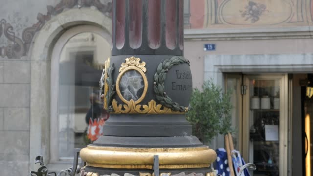 Stein am Rhein fountain in the marketplace- tilt up Camera starts at the basin of the fountain and tilts up the column to the statue of a soldier at the top. The soldiers shield shows St. George slaying the dragon. In the background are the frescoe houses of the marketplace. bay window stock videos & royalty-free footage