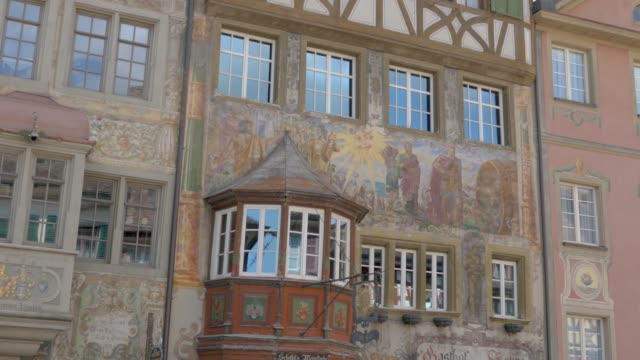 Stein am Rhein- frescoe buildings on the marketplace Camera pans right along the row of houses lining the marketplace, with fresco facades. Midway through the shot is the soldier statue and marketplace water fountain. bay window stock videos & royalty-free footage