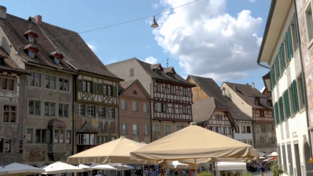 Stein am Rhein marketplace with frescoes- pan left Camera moves forward and then pans left in the marketplace square, showing the facades of houses decorated with frescoes. bay window stock videos & royalty-free footage