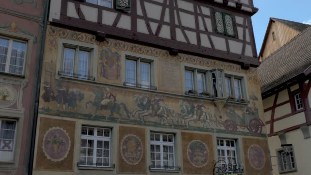 Stein am Rhein- pan right across painted buildings Camera pans right across frescoes painted on buildings in the marketplace square in Stein am Rhein. bay window stock videos & royalty-free footage