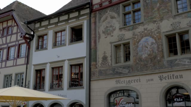 Stein am Rhein pedestrian street and marketplace Camera pans right across frescoes painted on buildings in the marketplace square, including historic House of the Pelican (German:Haus zum Pelikan) in Stein am Rhein. bay window stock videos & royalty-free footage