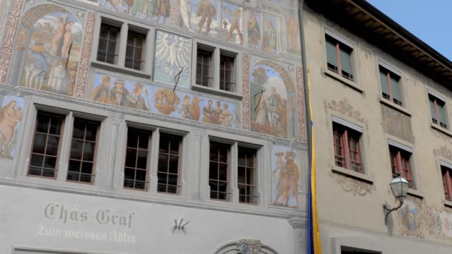 Stein am Rhein pedestrian street to market place- pan left House of the white eagle (German: Haus zum Weissen Adler) from 1520. Camera pans left across the facade with fresco. bay window stock videos & royalty-free footage
