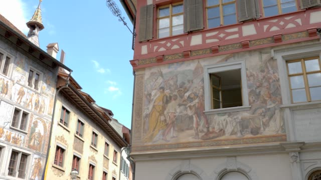 Stein am Rhein town hall- pan right Camera pans right from House of White Eagle (German:Haus zum Weissen Adler) to the town hall, both with frescoes on the facade. bay window stock videos & royalty-free footage