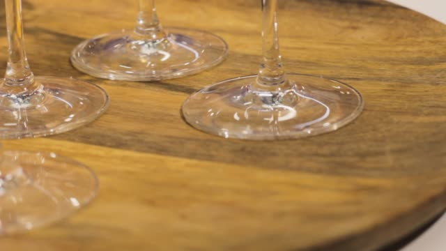stem of glass on a wooden stand drinks on a tray - stelo video stock e b–roll
