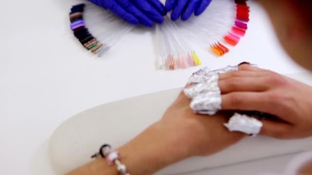 vidéos et rushes de étape du processus de manucure : pose de vernis en gel avec feuille pièces - cuticule