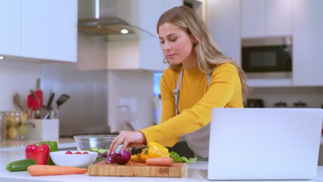 vídeos y material grabado en eventos de stock de paso uno: picar finamente las cebollas - woman cooking