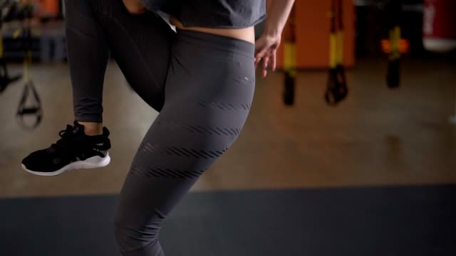 Step platforms. Girl in sports grey leggings and top doing exercises for aerobics. The concept of tightening in the gym for weight loss. Aimed footage of woman's torso video