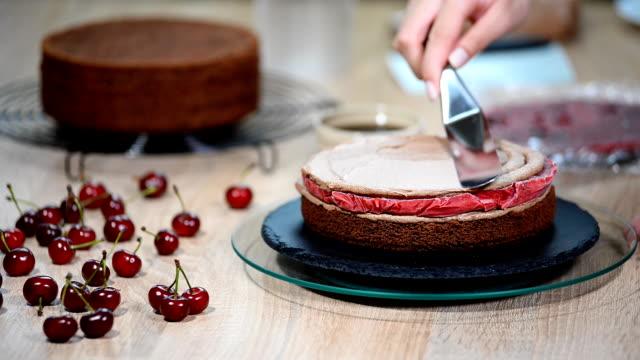 siyah tasarımcı pasta adım adım hazırlanması. pastacı pasta krema ile kapsar. - muhallebi stok videoları ve detay görüntü çekimi