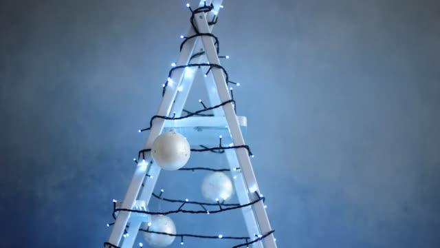 schrittleiter mit girlande, weihnachtsbaum dekorationen verziert - girlande dekoration stock-videos und b-roll-filmmaterial