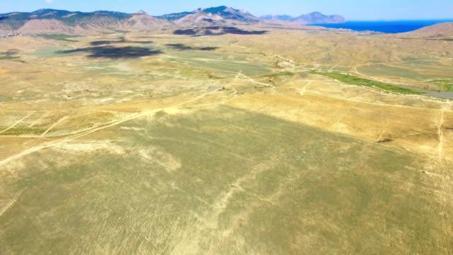 vídeos de stock, filmes e b-roll de antena: estepes e montanhas no fundo do céu azul - multicóptero