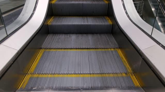 vídeos de stock, filmes e b-roll de passos de uma escada rolante em movimento - escada rolante