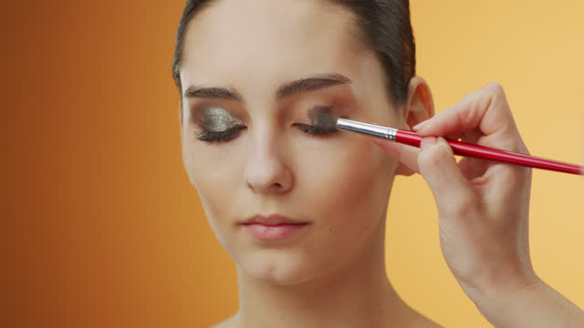 Steps of make-up applying. Close-up of a girl face, on whose eyelids a make-up artist applies brown shadows with a make-up brush. video