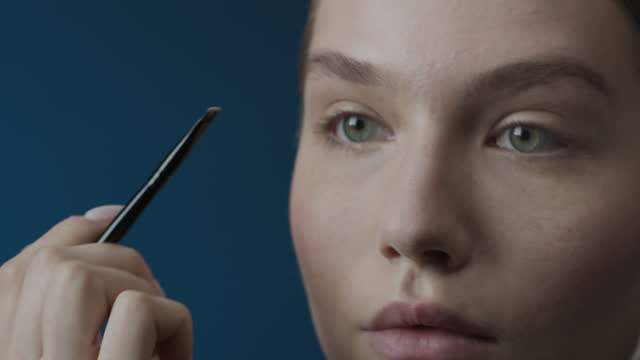 Steps of make-up applying. Close-up of the face of a girl who draws her eyebrows with a make-up brush. video