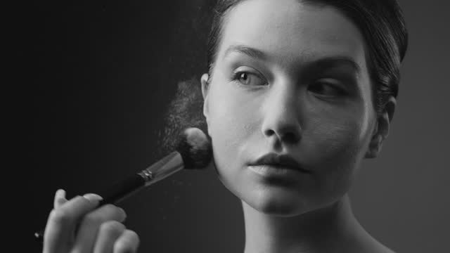 Steps of make-up applying. Close-up of the face of a young girl applying powder to her skin, and a cloud of texture is visible. Black and white video. video